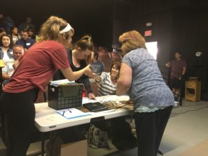Stage Manager Sonja Wittlieb passes out forms